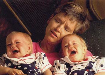 gemelos llorando y madre estresada
